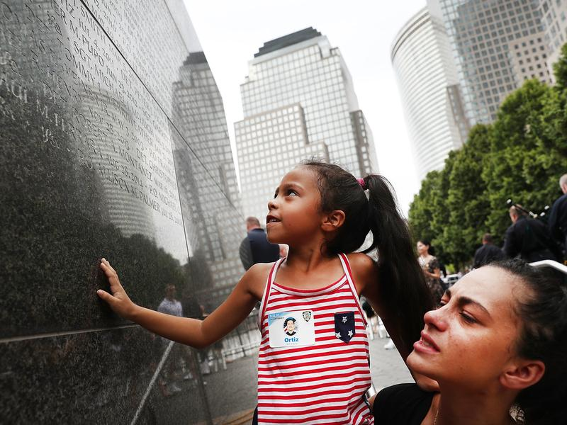 Bernadette Ortiz holds up her daughter, Adriana, as she looks for the name of her grandfather, New York City Police officer Edwin Ortiz, at a wall commemorating fallen officers in New York City. Families gathered at the wall following a procession in Lower Manhattan to mark the 15th anniversary of the Sept. 11 attacks and the officers who were killed during them and afterward.