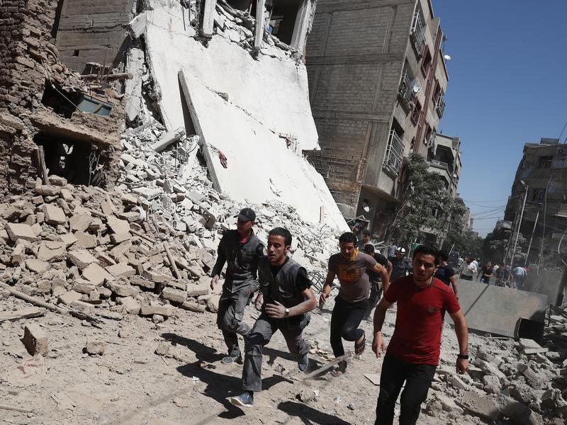 Syrians run for cover during reported government air strikes in the rebel-held town of Douma, east of the capital Damascus, on Sept. 9. Under the plan announced Friday, hostilities are to cease starting at sundown Sept. 12, the start of the Eid al-Adha holiday.