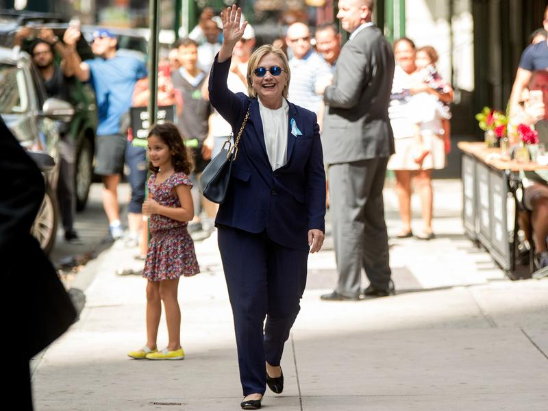 Hillary Clinton waves as she leaves an apartment building Sunday. Earlier in the day, she fell ill at a Sept. 11 commemoration event.