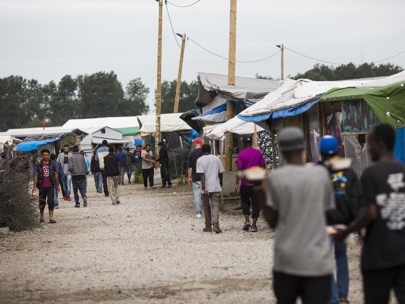 """Migrants walk past makeshift shops and shelters at a camp known as """"The Jungle"""" in Calais, France, on Sept. 6. Overcrowding has become an issue in the camp. """"I imagined a little camp,"""" says Calais resident Nicole Cordier, who has protested against The Jungle. """"Not an immense camp like this one. This is a city."""""""
