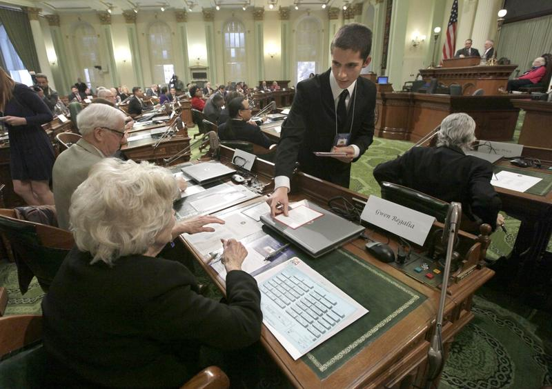 Electoral College member Christopher Tumbeiro, right, passes a ballot to Gwen Regalia, before the votes were taken for president and vice president, at the Capitol in Sacramento, Calif., Monday, Dec. 17, 2012. (Rich Pedroncelli/AP)