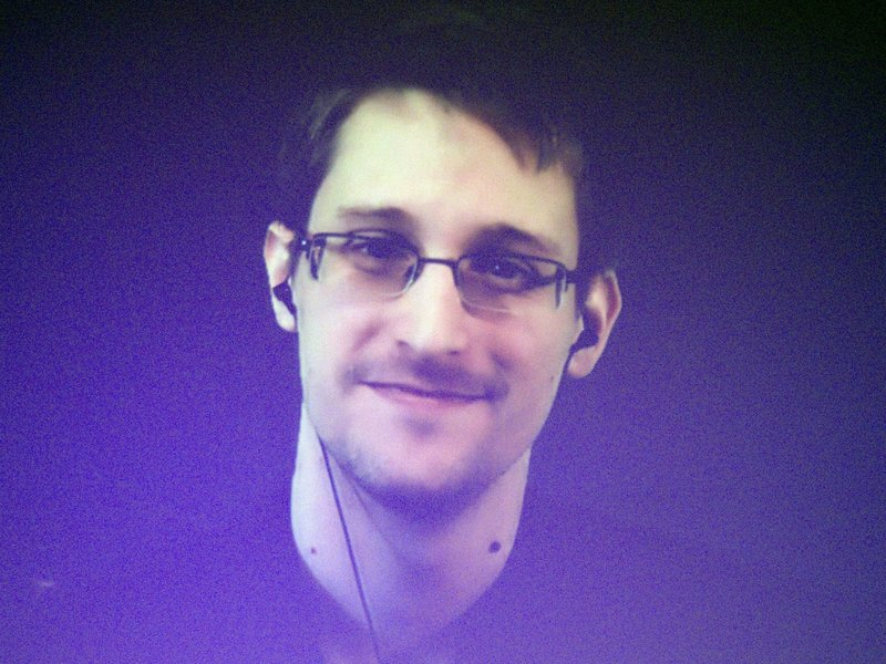 """Edward Snowden, who is in Moscow, is seen on a giant screen during a live video conference for an interview as part of an Amnesty International event in Paris in December 2014. The House Permanent Select Committee on Intelligence published a summary report accusing Snowden of causing """"tremendous damage to U.S. national security."""""""