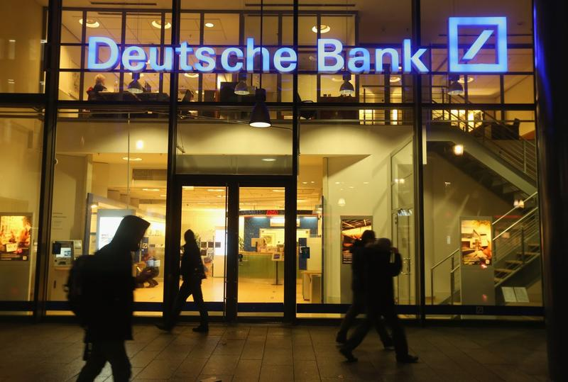 People walk past a branch of Deutsche Bank on Feb. 9, 2016 in Berlin, Germany. The Justice Department asked the bank to pay $14 billion to settle an investigation into risky mortgage practices leading up to the financial crisis. (Sean Gallup/Getty Images)