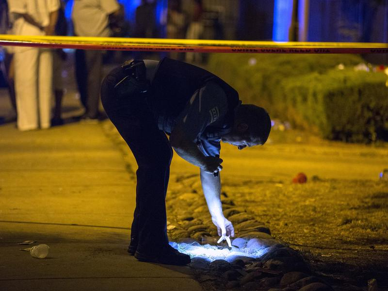 A police officer looks at evidence at the scene of a fatal shooting on Aug. 6 in the University Village neighborhood of Chicago.
