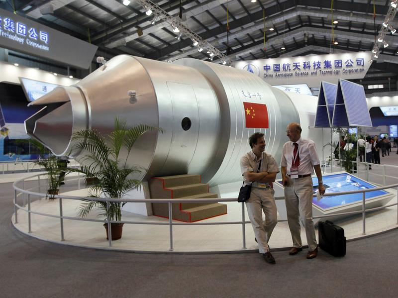 Visitors stand beside a model of the Tiangong-1 space lab in 2010, at the 8th China International Aviation and Aerospace Exhibition in Zhuhai, China. The real Tiangong-1 was launched into space in 2011 and will be returning to Earth next year — with some observers speculating China has lost control over the spacecraft.