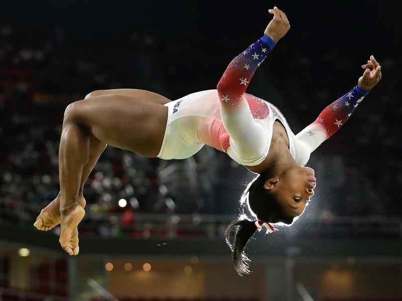 Simone Biles flies through the air while performing on the balance beam at the Olympics in Rio de Janeiro.