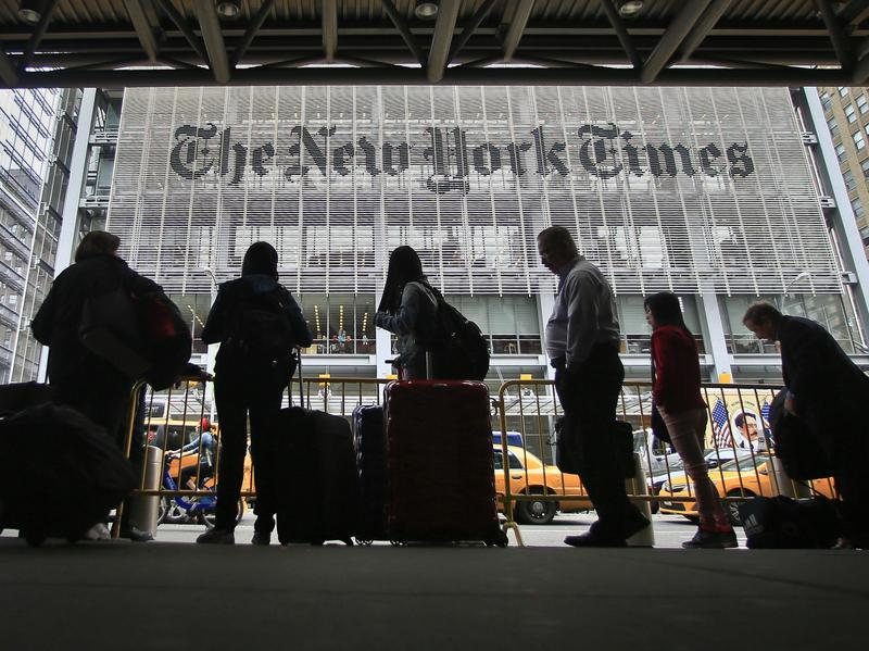Pedestrians wait for cabs across the street from <em>The New York Times</em> in 2014.