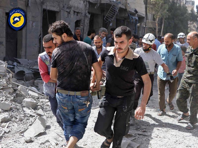 White Helmet rescue volunteers work at the site of airstrikes in the rebel-held al-Mashhad neighborhood in eastern Aleppo on Wednesday.