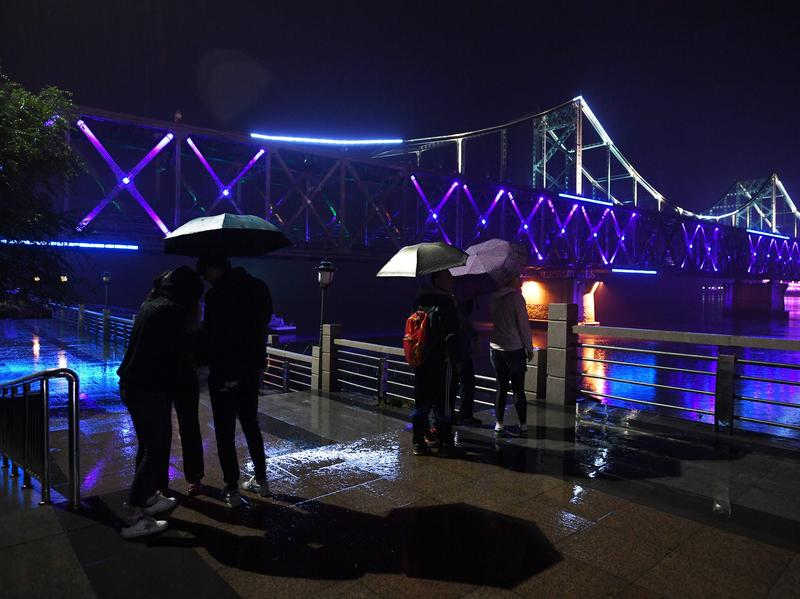 Visitors look at the China-North Korea Friendship Bridge across the Yalu River from Dandong, in northeast China. A company operating from Dandong is under fresh sanctions by the U.S.