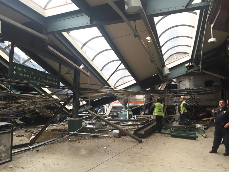 People examine the wreckage of a New Jersey Transit commuter train that crashed into the station in Hoboken, N.J., during the morning rush hour Thursday.