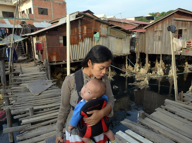 A Cambodian woman carries her baby and walks past a wooden bridge over a polluted canal in Phnom Penh in 2013. Cambodia was one of several countries the World Bank studied where income inequality declined in recent years.
