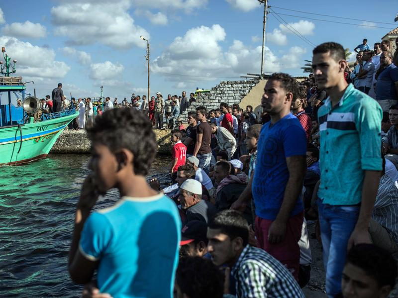 Egyptians wait on shore in Rosetta on Sept. 22 as a coast guard boat arrives carrying the bodies recovered from a boat that capsized off Egypt's Mediterranean coast.