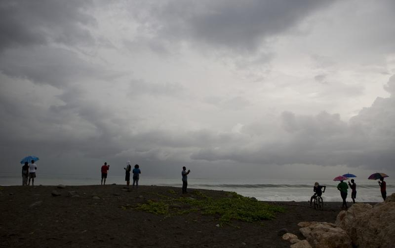 People watches the clouds and the sea in the outskirts of Kingston, Jamaica, Sunday, Oct. 2, 2016. (Eduardo Verdugo/AP)