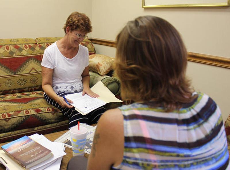 Peer support sepcialist Sally Moore (left) gives a needs assessment to Deana Kilpatrick at PEEPs in Recovery in Reeds Spring, Mo. (Bram Sable-Smith/KBIA/Side Effects Public Media)