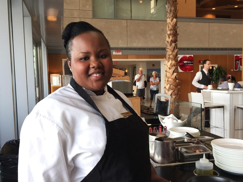 Florance Eloi works the omelet station at Hilton's Conrad Miami. By the time Eloi gave birth, a new company policy guaranteed her 10 weeks of fully paid parental leave.