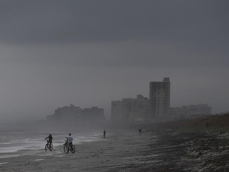 People bike on the beach ahead of Hurricane Matthew in Atlantic Beach, Fla., on Wednesday. Droves of people in the U.S. have begun evacuating coastal areas ahead of the storm, which tracked a deadly path through the Caribbean in a maelstrom of wind, mud and water.