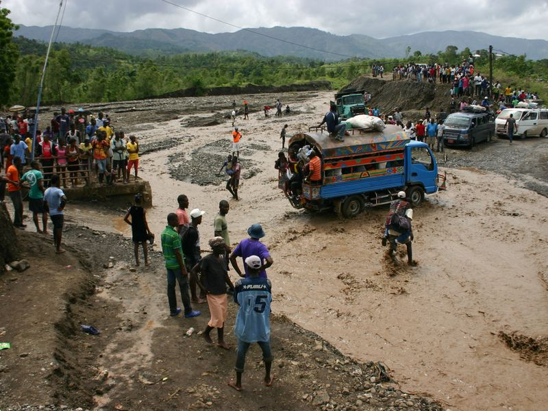 Haitians watch as people cross a river on National Route 2. Hurricane Matthew washed out a bridge at this spot cuttting off much of the southwest of the country from the capital Port au Prince.
