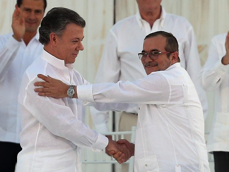 Colombia's President Juan Manuel Santos (left) shakes hands with the top commander of the FARC rebels, Rodrigo Londono, after signing a peace agreement on Sept. 26. Santos was named winner of the Nobel Peace Prize on Friday.