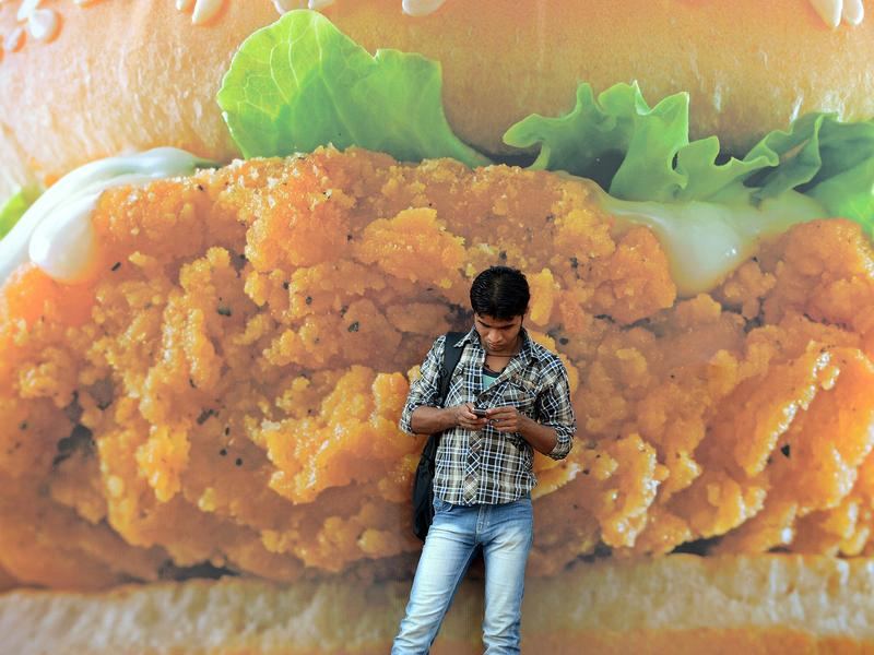 An Indian pedestrian checks his mobile phone in front of an advertisement for a burger of a fast-food giant in Mumbai, India. Fast food and highly processed foods and sodas are increasingly becoming more popular around the world, one of the main reasons for increasing rates of overweight and obesity.