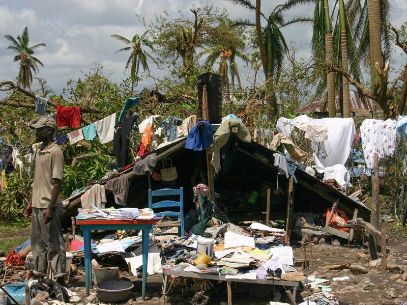 Gilbert Lorcy outside his home in Les Cayes. He was able to put the roof — which blew off in the storm — on the low stone walls of the foundation. His family spends days at the house and sleeps in a shelter at night.