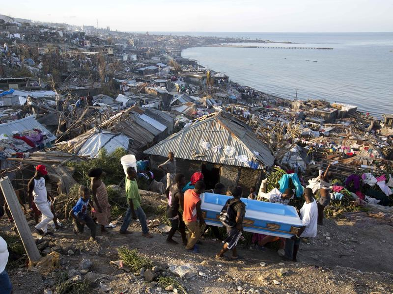 Residents carry a coffin containing the remains of a pregnant woman killed by Hurricane Matthew, in Jeremie, Haiti. People across southwest Haiti are salvaging what they can from wreckage the Category 4 storm caused.