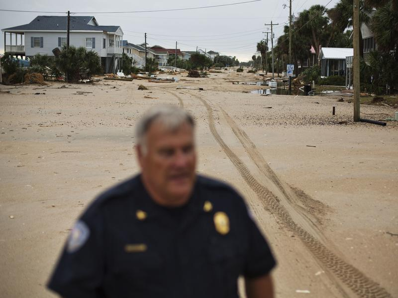 Chief of Police George Brothers walks along what used to be a four-lane national scenic byway that's now covered in sand after Hurricane Matthew hit the beach community of Edisto Beach, S.C., Saturday.