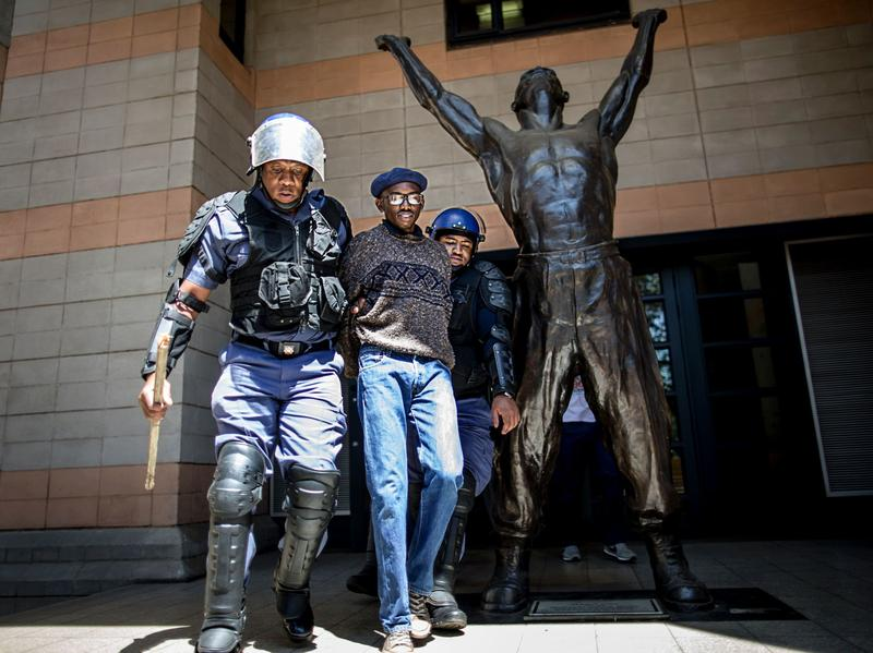 A student is detained by a South African policeman after he entered a building of Witwatersrand University. Protesters disrupted classes and demanded free tuition.