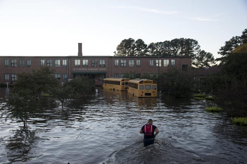 A volunteer firefighter with the Raynham-McDonald Fire Department makes his way through floodwaters caused by rain from Hurricane Matthew to turn off the lights of a school bus in front of W.H. Knuckles Elementary School in Lumberton, N.C., Monday, Oct. 10, 2016. (Mike Spencer/AP)