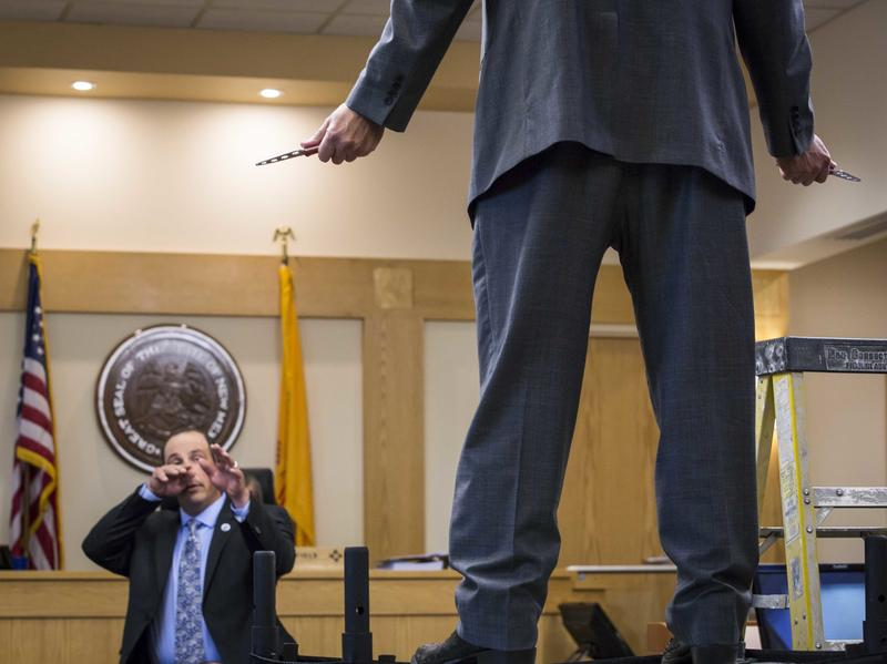 In a photo taken Oct. 6 during the trial, former Albuquerque police Officer Keith Sandy, demonstrates his position during a 2014 shooting. His attorney, on a table, plays the part of James Boyd, who Sandy and another former officer are accused of murdering.