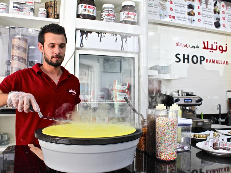 A man flips a crepe at the Nutella Shop off of Rukab Street in Ramallah, in the West Bank.