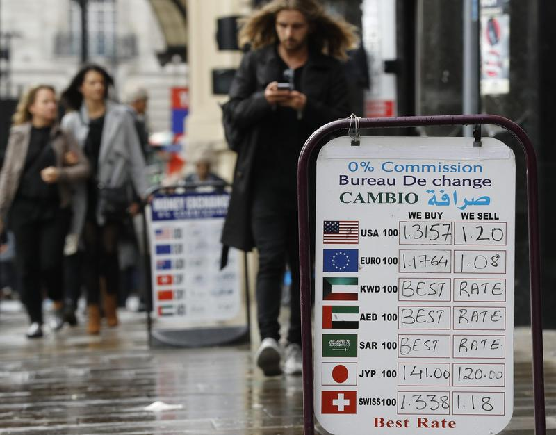 People pass currency exchange boards in London, Wednesday, Oct. 12, 2016. (Frank Augstein/AP)