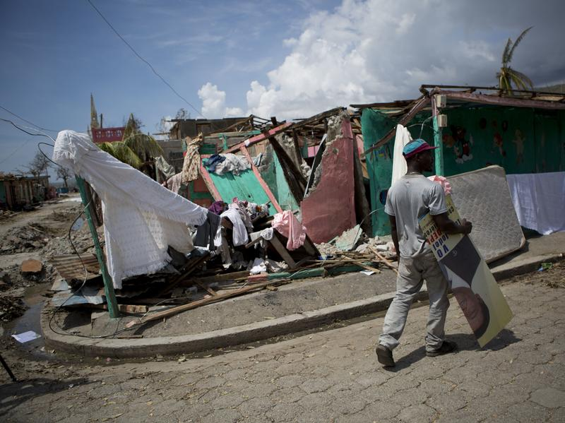 A man carries a presidential election poster past a destroyed kindergarten in Les Anglais, Haiti, on Monday.