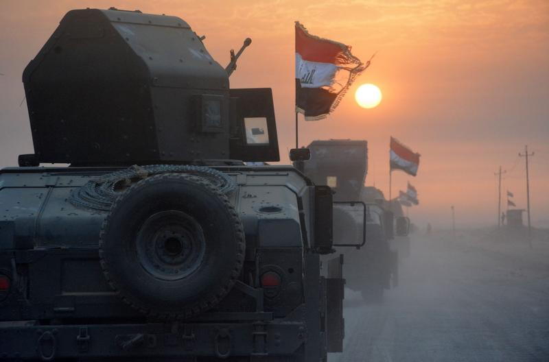 Pro-government forces drive in military vehicles in Iraq's eastern Salaheddin province, south of Hawijah, on Oct. 10, 2016, as they clear the area in preparation for the push to retake the northern Iraqi city of Mosul, the last Islamic State (IS) group-held city in Iraq. (Mahmoud Al-Samarrai/AFP/Getty Images)