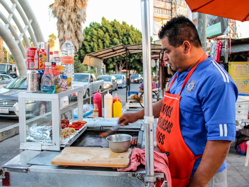 Carlos Rodriguez grills bacon-wrapped hot dogs on his food cart. Next to him, his family sells churros from their other food cart.