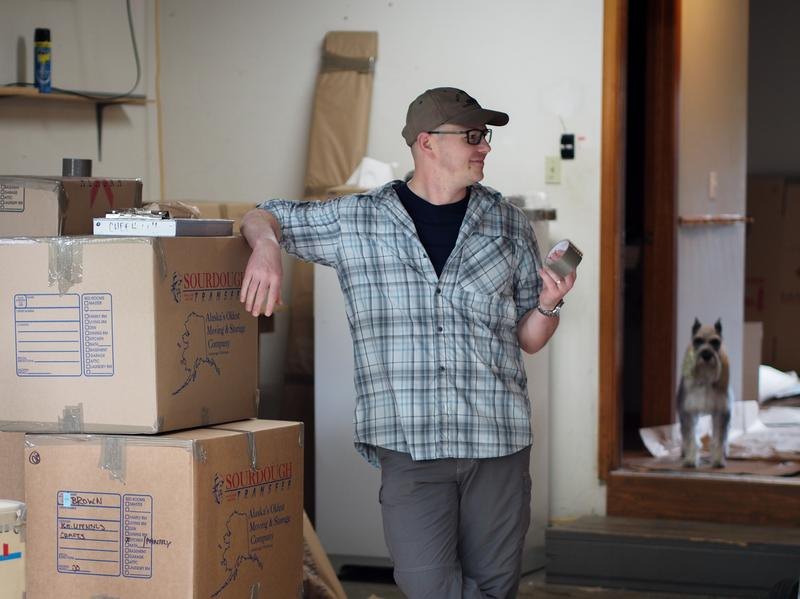 Lt. Col. Alan Brown stands in his garage, filled with boxes that will be sent to the family's new home in New York. In the background is Lucy, the family's Schnauzer.