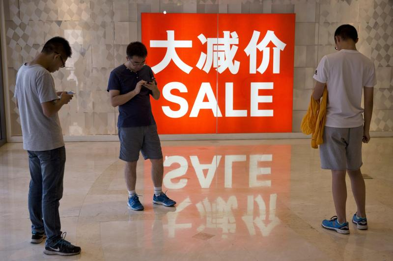 In this July 10, 2016 file photo, Chinese shoppers stand near a sale advertisement at a shopping area in Beijing. The world's second-largest economy grew by 6.7 percent in the three months ending in September compared with a year earlier, data showed Wednesday, Oct. 19, 2016. (Ng Han Guan/AP)