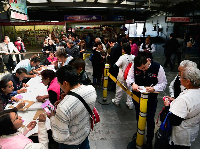 Subway passengers receive whistles at the Pantitlan Metro Station in Mexico City in July as part of a campaign aimed at preventing sexual assaults against women on public transportation.