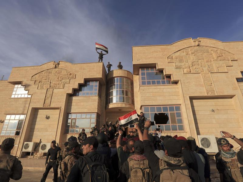 Iraqi forces raise a flag after retaking Bartella, a town nine miles outside Mosul, Iraq, on Friday. Iraq's army, backed by U.S. air power, began an offensive this week to retake Mosul, the last city in Iraq controlled by the Islamic State. Some smaller towns and villages were retaken this week, but the Iraqis have not yet reached Mosul.