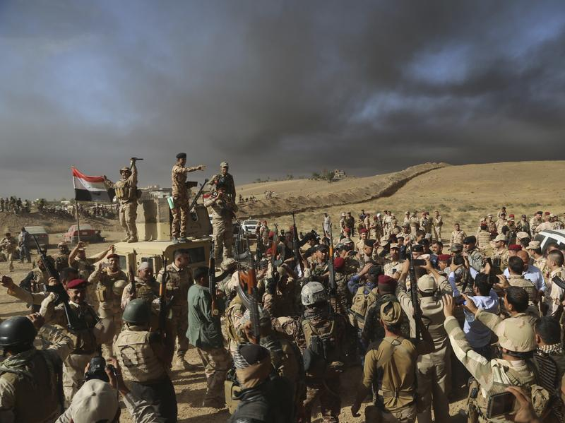 Iraqi army soldiers raise their weapons Thursday in celebration on the outskirts of Mosul, Iraq.