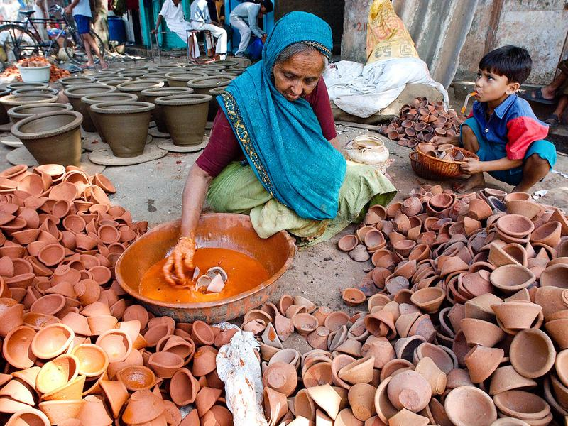 Ratnaram Diwala, 70, colors traditional earthern oil lamps at Kumbharwada. She's part of the potters colony — some 500 families — living inside the Dhavari slum area in central Mumbai.