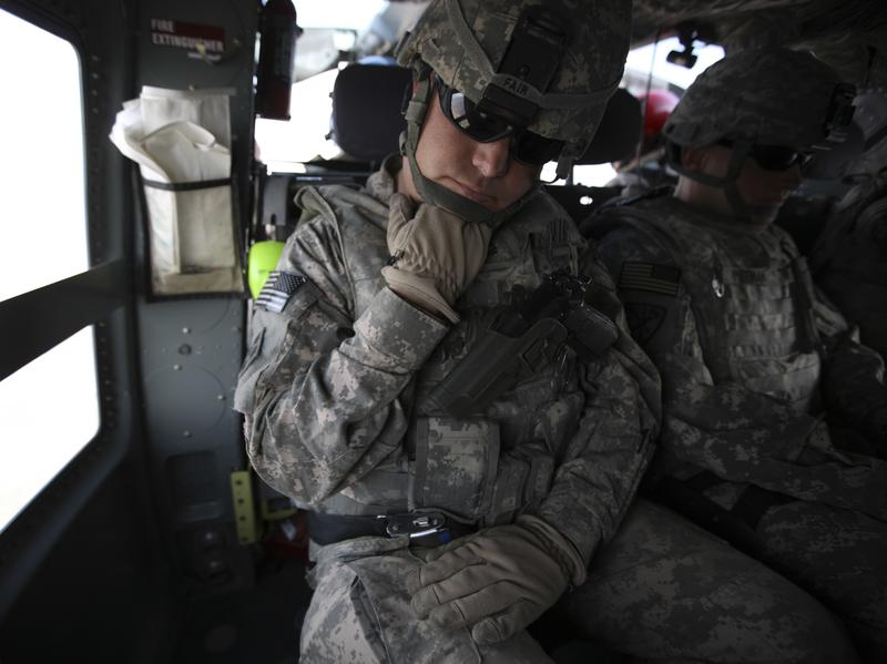 The Pentagon is seeking millions of dollars from nearly 10,000 current or former soldiers in the California National Guard, saying they weren't eligible for re-enlistment bonuses. Here, soldiers from the state's guard force are seen in 2010, resting during transport in northeastern Afghanistan.