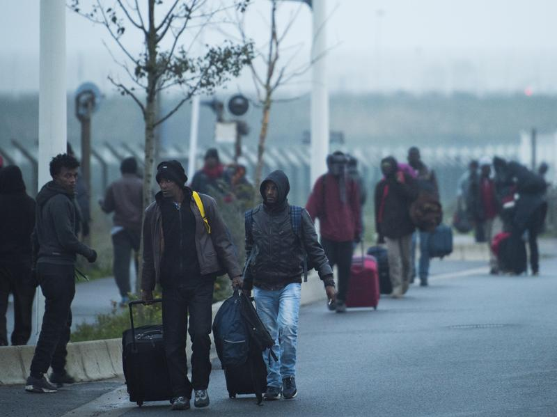Migrants arrive to register for relocation at a temporary facility outside The Jungle refugee camp near the port of Calais, France. The camp known for its squalor housed an estimated 6,100 migrants.