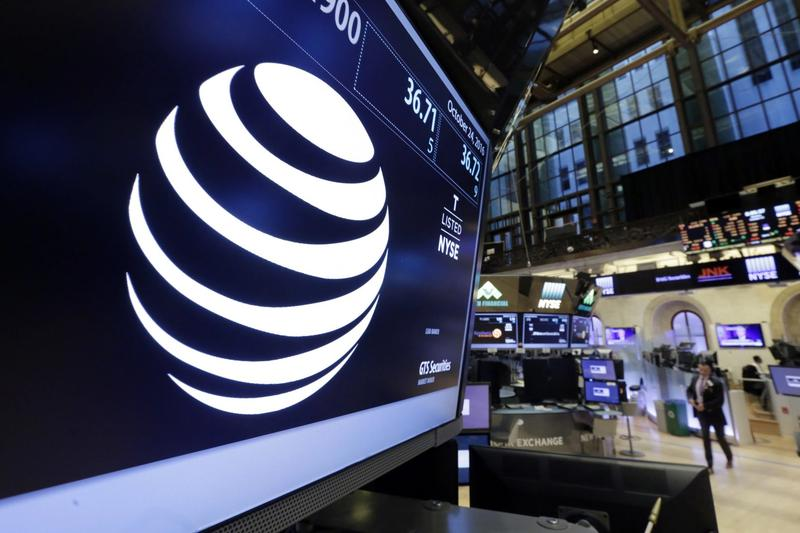 The AT&T logo appears above the post where it trades on the floor of the New York Stock Exchange, Monday, Oct. 24, 2016. AT&T's $85.4 billion purchase of Time Warner represents a new bet on synergy between companies that distribute information and entertainment to consumers and those that produce it. (Richard Drew/AP)