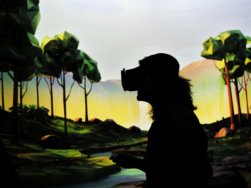 """A woman tries on Google's virtual reality device """"Daydream View"""" after the opening of Google's pop-up store in New York on October 20, 2016."""