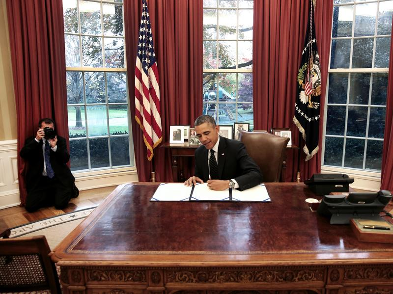 Official White House Photographer Pete Souza photographs President Barack Obama as he signs a bill in the Oval Office at the White House, on Nov. 21, 2013.