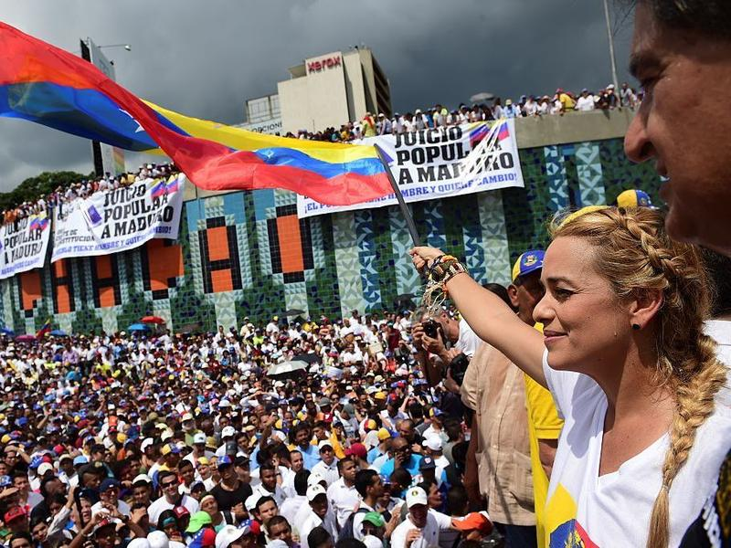 Lilian Tintori, wife of prominent jailed opposition leader Leopoldo Lopez, waves a Venezuelan flag during a rally against the government of President Nicolas Maduro in Caracas on Wednesday.