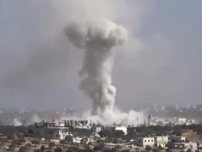 Smoke rises in the distance after an airstrike Wednesday on the village of Hass, Syria, where teachers and students were killed.