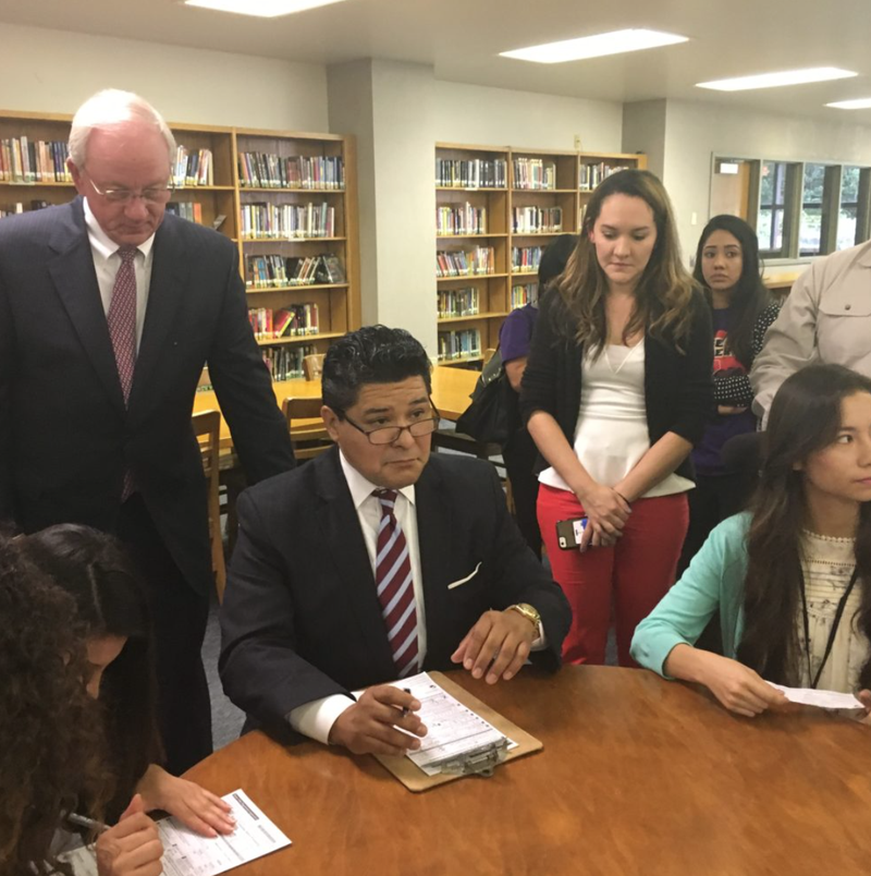 Richard Carranza, Houston ISD Superintendent, a recent arrival from California, registers as a Texas voter alongside students at Sam Houston Math, Science, and Technology Center. Mike Sullivan, Harris County Tax Assessor-Collector, looks on. (Andrew Schneider/Houston Public Media)