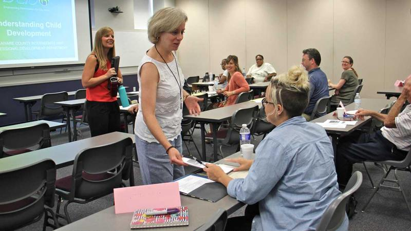 Professional development specialist Nora Connell hands out materals during a class for prospective substitute teachers at the Delaware County Intermediate Unit. (Emma Lee/WHYY)