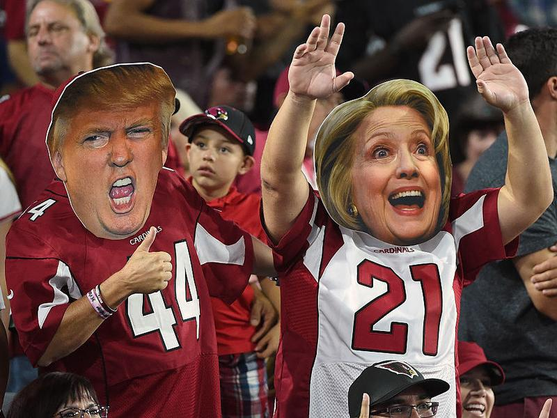 Arizona Cardinals fans wear masks of Presidential candidates Donald Trump and Hillary Clinton during the NFL game between the New York Jets and Arizona Cardinals Oct. 17, 2016.